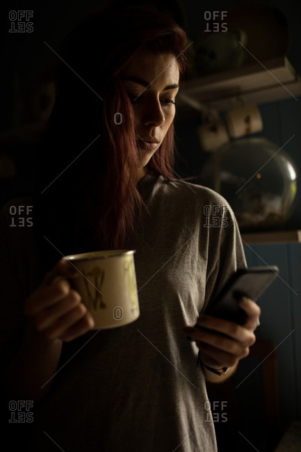 Young woman holding coffee mug and text messaging on the mobile phone at home