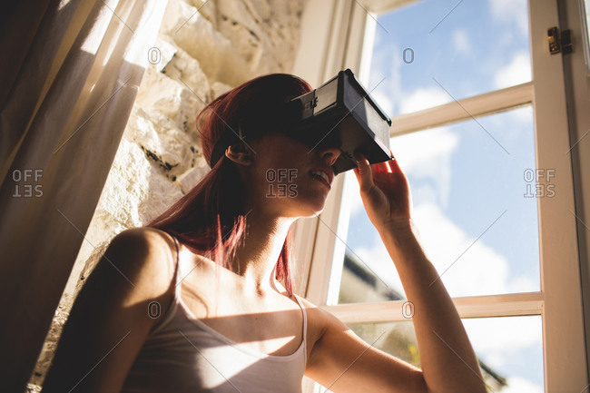 Young woman using the virtual reality headset at home