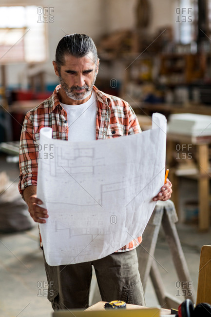 Carpenter looking at a blueprint in workshop