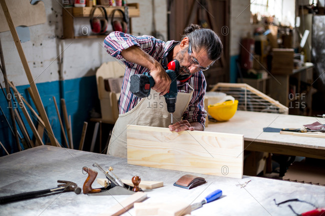 Carpenter drilling a hole in a wooden plank at the workbench