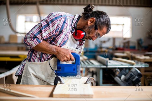 Carpenter using jigsaw in workshop