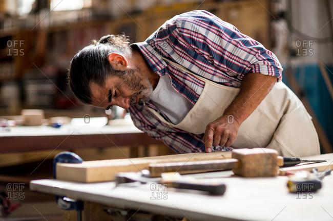 Carpenter working on wooden plank at workshop