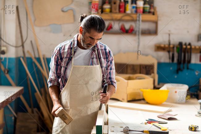 Carpenter using mallet and chisel in workshop