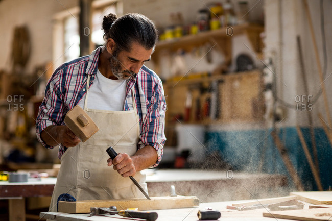 Carpenter carving wood with chisel in workshop