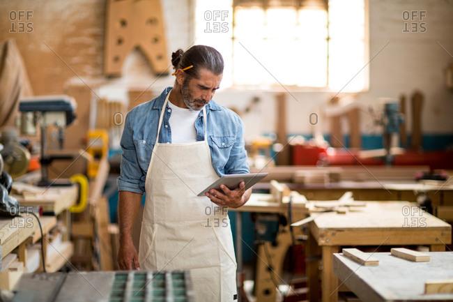 Carpenter standing in workshop and using digital tablet