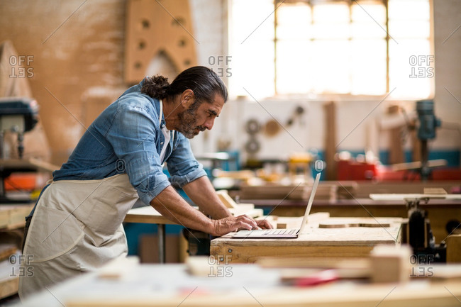 Carpenter standing in workshop and using laptop
