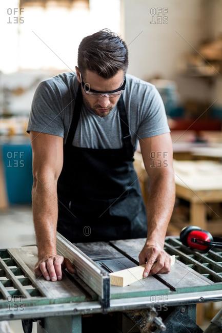 Carpenter working on wooden plank in workshop