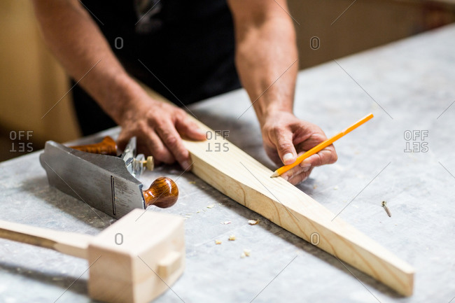 Carpenter marking on wooden plank with pencil in workshop