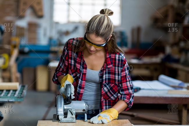 Female carpenter using jigsaw in workshop