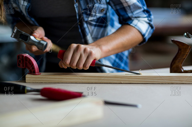 Mid section of female carpenter using chisel on wooden plank in workshop