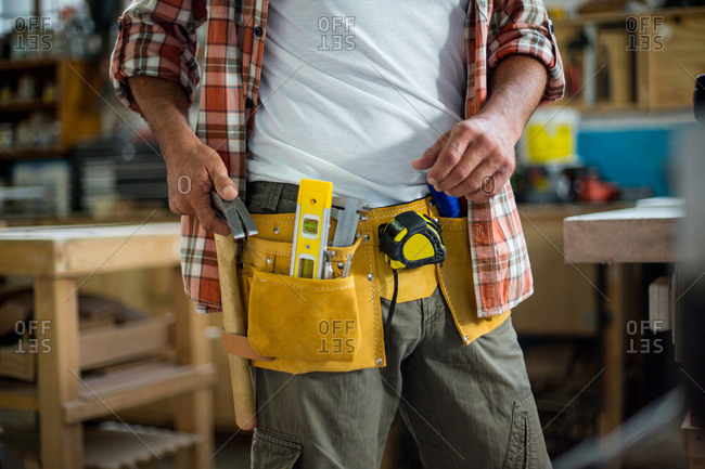 Mid section of carpenter removing hammer from tool belt in workshop