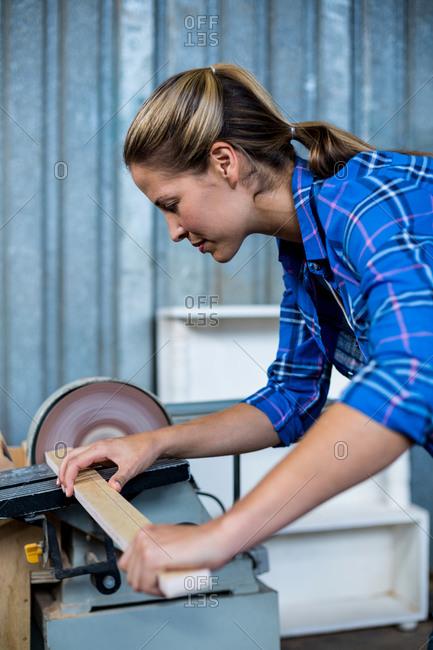 Female carpenter working with sanding machine in workshop