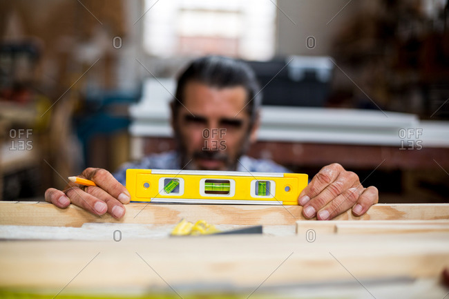 Carpenter measuring a length of wooden plank with spirit level in workshop