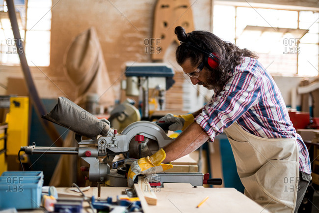 Carpenter cutting wooden plank with circular saw in workshop