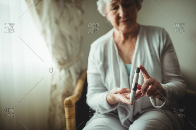 Senior woman holding a blood glucose monitor in a retirement home