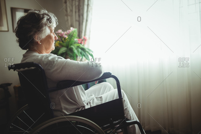 Senior woman sitting in a wheelchair in a retirement home