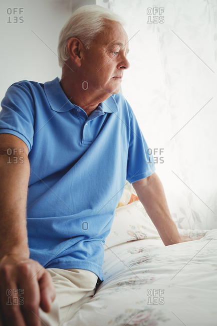 Thoughtful senior man sitting on his bed in a retirement home