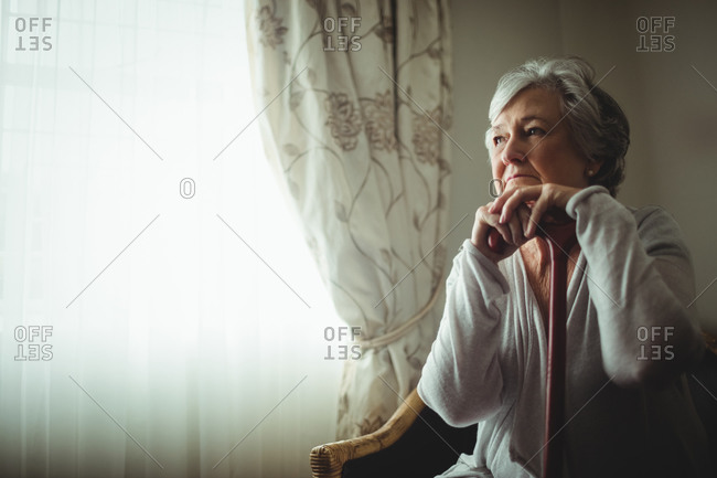 Thoughtful senior woman sitting on a chair in a retirement home