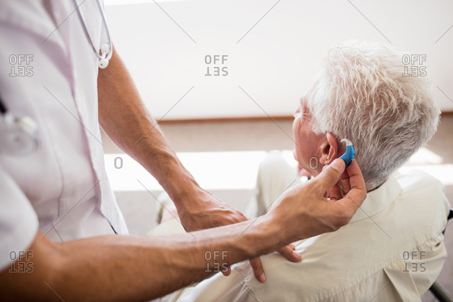 Nurse giving hearing device to a senior man in a retirement home