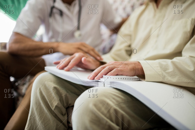 Blind senior man using braille to read in a retirement home