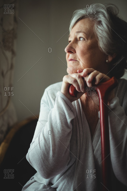 Thoughtful senior woman with cane in a retirement home