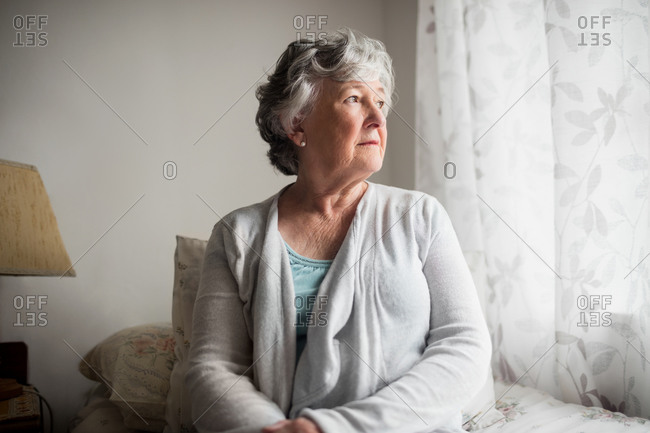 Thoughtful businesswoman sitting on her bed in a retirement home