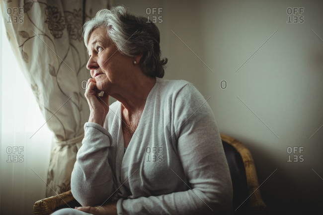 Thoughtful woman looking outside in a retirement home