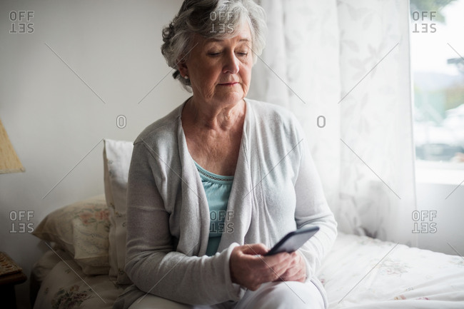 Senior woman sending a message with her smartphone in a retirement home