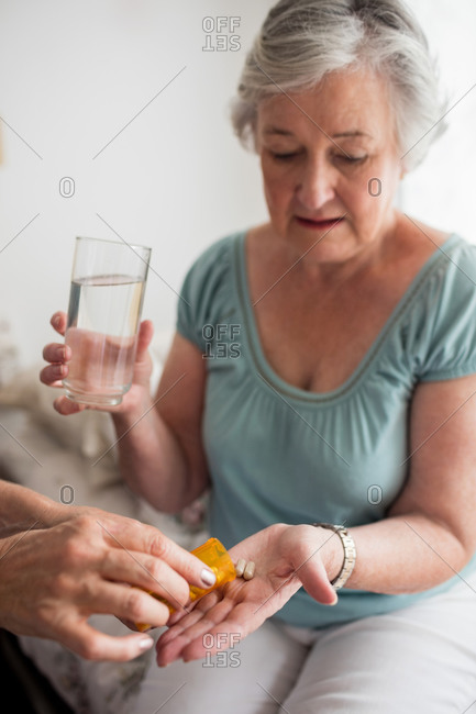 Nurse giving medicaments to a senior woman in a retirement home
