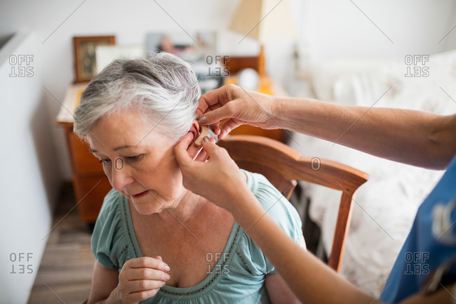 Nurse putting hearing aid to a senior woman in a retirement home