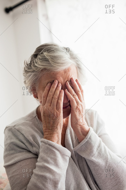 Senior woman hiding her face with her hands in a retirement home