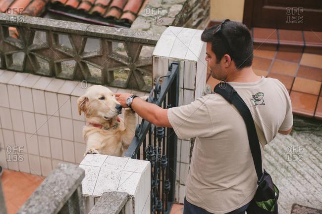 August 26, 2014: Man petting dog behind gate
