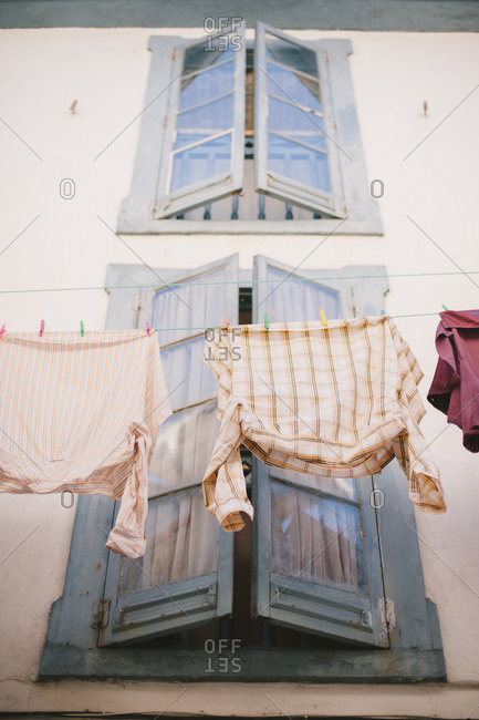 Laundry hanging by shuttered windows