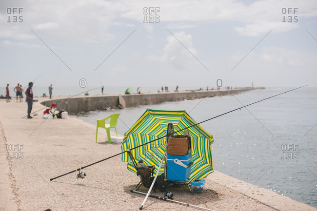 Umbrella and fishing gear on pier