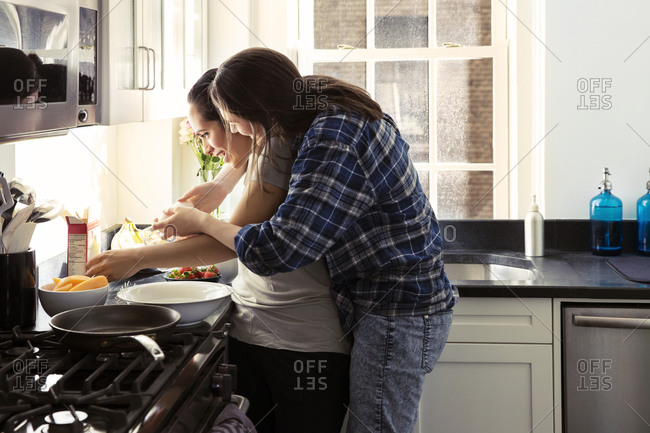 Side view of affectionate gay couple spending quality time in kitchen