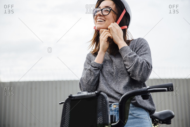 Low angle view of happy woman wearing helmet while sitting on bike