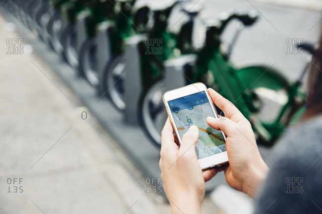 High angle view of woman using smart phone by bicycle rack on street