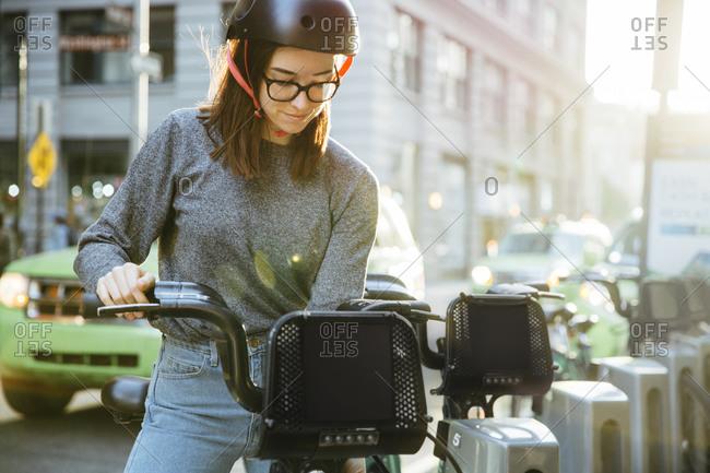 Young woman unlocking bike on street