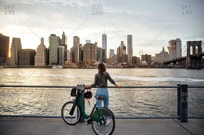 Rear view of woman with bike looking at city view while standing on observation point