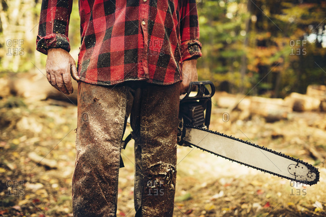 Midsection of lumberjack holding chainsaw in forest