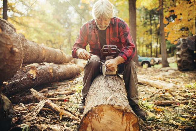 Mature male lumberjack fixing chainsaw while sitting on log in forest