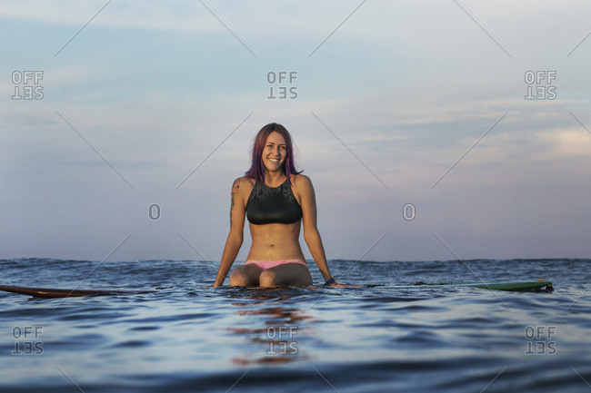 Happy woman sitting on surfboard in sea during sunset