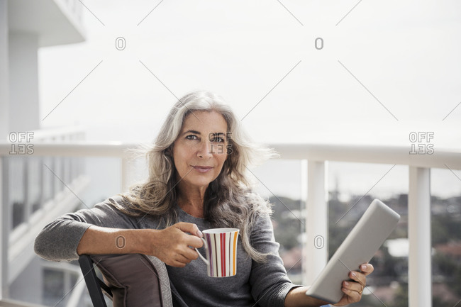 Portrait of confident mature woman holding tablet computer and coffee mug on balcony