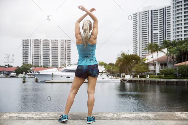 Rear view of mature woman exercising on footpath by river