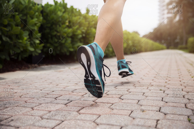 Low section of mature woman running on footpath