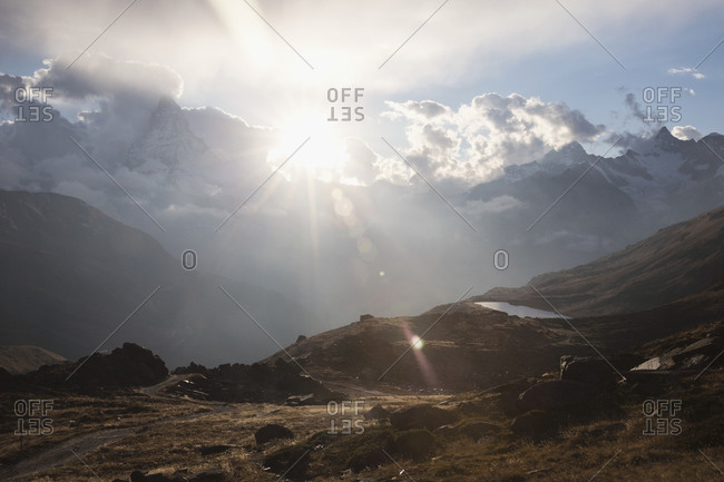 Bright sun over mountains against cloudy sky