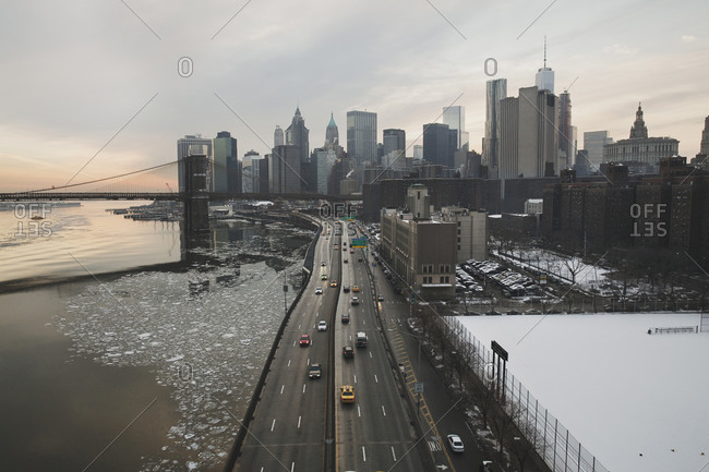 Cityscape by Brooklyn Bridge against cloudy sky during sunset