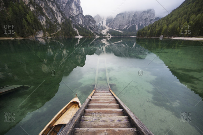 Wooden steps on lake by mountains