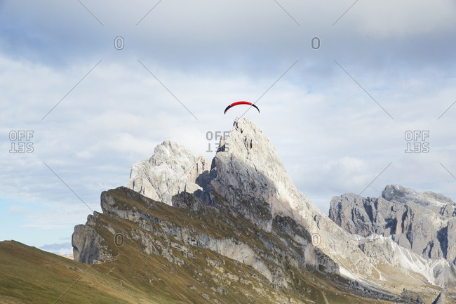 Low angle view of parachute over mountain against cloudy sky