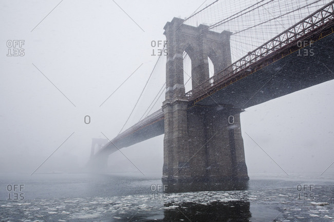 Low angle view of Brooklyn Bridge in foggy weather